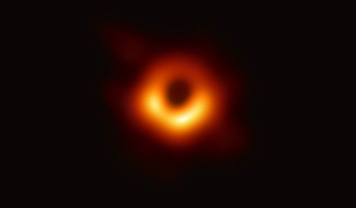 Svartur skuggi sjóndeildar svartholsins sést í miðju gulleitrar efnisskífunnar sem umlykur það í miðju Messier 87-vetrarbrautarinnar.
