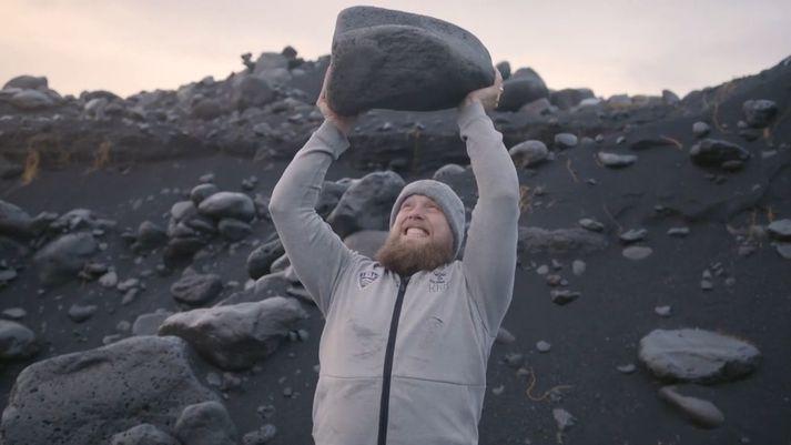 Kári Kristján Kristjánsson með stein á lofti í fjörunni.