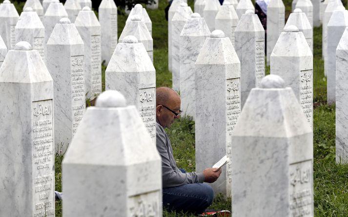 Maður á bæn við minnisvarða um fórnarlömb fjöldamorðsins í Srebrenica.