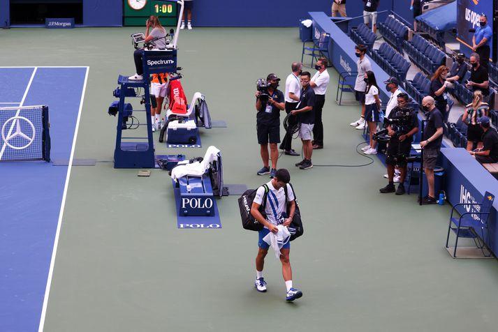 Djokovic yfirgefur völlinn eftir að hafa verið dæmdur úr leik.