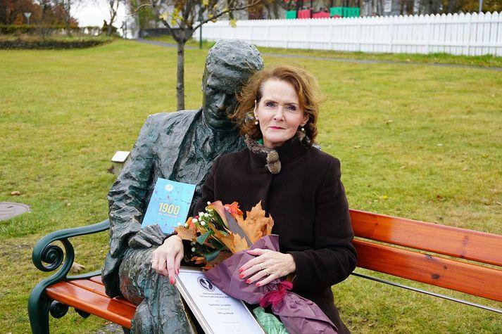 Ragnheiður Lárusdóttir tók við verðlaunaskjali og blómvendi við styttu skáldsins Tómasar Guðmundssonar fyrr í dag.