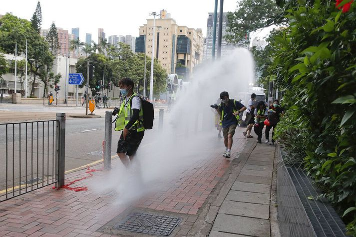 Lögreglan í Hong Kong sést hér beita vatni gegn blaðamönnum sem fylgdist með aðgerðum hennar í borginni í gær.