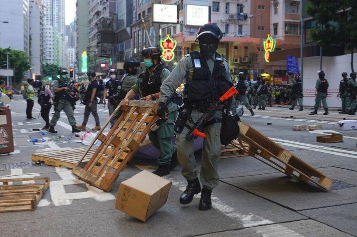 Lögregla fjarlægir vegatálma sem mótmælendur höfðu reist í Hong Kong.