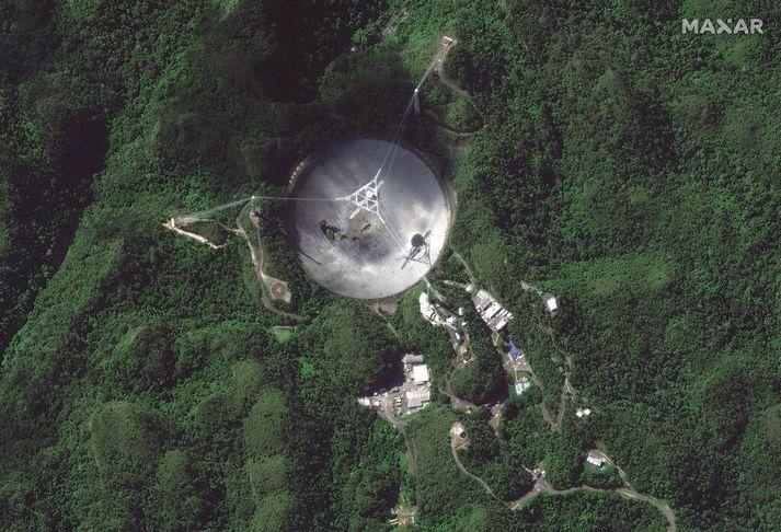 Gervihnattarmynd af Arecibo-útvarpssjónaukanum 17. nóvember. Móttökutækið sést hanga yfir miðju disksins. Það hrundi endanlega í dag.