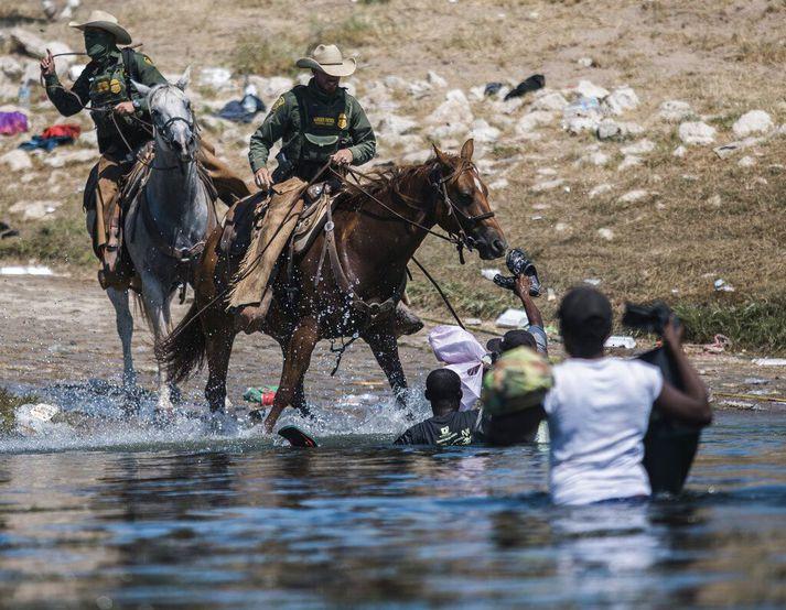 Bandarískir landamæraverðir á hestbaki reyna að fanga farandfólk sem kemur yfir Río Grande-fljót á landamærum Bandaríkjanna og Texas á sunnudag.