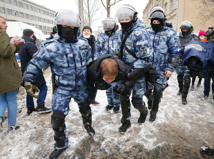 Óeirðalögregla heldur á handteknum mótmælanda í Moskvu.
