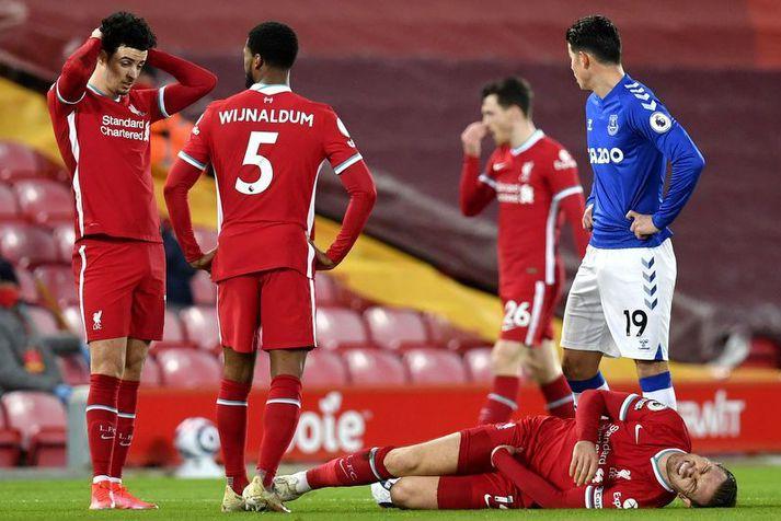 Jordan Henderson liggur sárþjáður í grasinu eftir að hafa meiðst í leik Liverpool og Everton á Anfield um síðustu helgi.