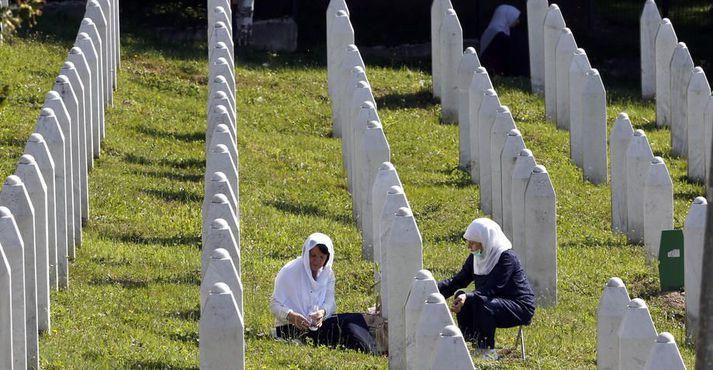 Konur kveikja á kertum í kirkjugarðinum fyrir alla þá sem létust í þjóðarmorðunum árið 1995 í Srebrenica.