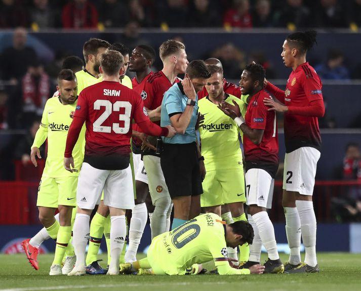 Lionel Messi liggur í grasinu en Chris Smalling  er lengst til hægri.