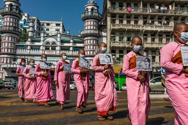 Munkar mótmæla valdaráninu í Mjanmar og halda uppi myndum af Aung San Suu Kyi og krefjast þess að hún verði leyst úr haldi.