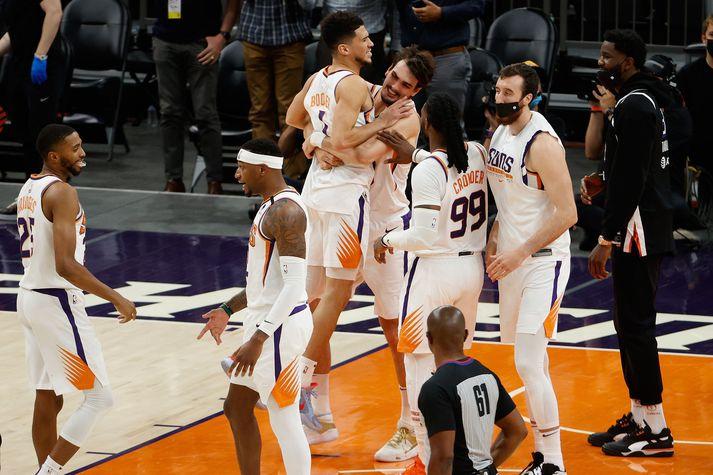 Samherjar Devins Booker fagna með honum eftir að hann tryggði Phoenix Suns sigur á Portland Trail Blazers.