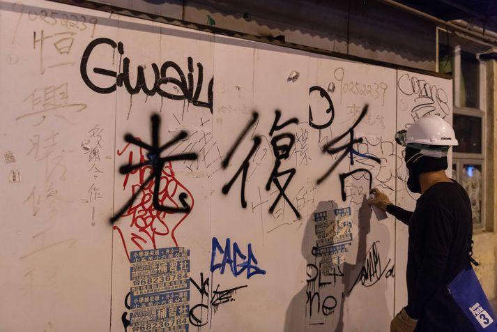 Lýðræðissinni skrifar slagorð á vegg í Hong Kong.